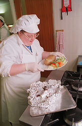Woman with Downs Syndrome putting baked potato onto plate,