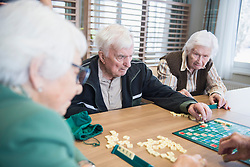 Senior inhabitants playing board game in rest home