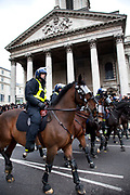 "Police horses in riot gear pass St Martin in the Fields church as students march through central London to protest against rises in tuition fees and changes to higher education. The police were out in force as thousands of students marched through central London. Some 4,000 officers were on duty, as demonstrators marched peacefully in a protest against higher tuition fees and ""privatisation"" in universities. The police estimated that about 2,000 people took part in the demonstration."