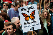 March against austerity, London June 20th 2015. A protester holds a placard saying 'Migration is beautiful'.