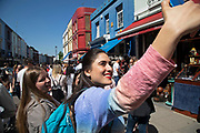 Young women take a selfie with their mobile phone on Portobello Road Market in Notting Hill, West London, England, United Kingdom. People enjoying a sunny day out hanging out at the famous Sunday market, when the antique stalls line the street.  Portobello Market is the worlds largest antiques market with over 1,000 dealers selling every kind of antique and collectible. Visitors flock from all over the world to walk along one of Londons best loved streets.