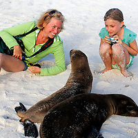 South America, Ecuador, Galapagos Islands. Mother and daughter meet baby sea lions in the Galapagos Islands.