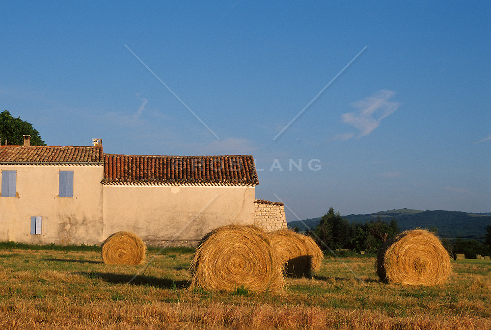 Haystacks at sunset in a field near a house in France