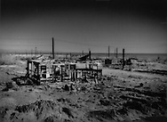 Deserts are scattered with ghost towns: Ruined home and abandoned neighborhood on the shores of the Salton Sea (seen in background), which sits below sea level, after farm runoff raised lake waters and  flooded this part of Bombay Beach several years before reducing the neighborhood to a ghost town, Sonora Desert, California, USA.