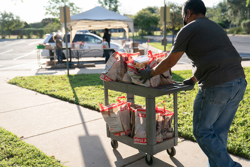 Staff members conduct a twice-weekly fresh food drive sponsored by Catholic Charities helping low-income Texans  make ends meet in Austin. The October 1, 2020 effort helped several hundred family members with fruit, meats, milk and cereal.
