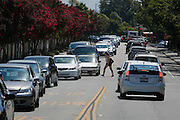 A student crosses through after-school traffic on Escuela Parkway near Milpitas High School in Milpitas, California, on August 19, 2013. (Stan Olszewski/SOSKIphoto)