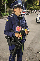 March 16, 2019 - Christchurch, Canterbury, New Zealand - Police officer stands guarding the mosque shooting cordon with a pistol, automatic rifle, bullet proof vest and a flower after the Christchurch mosques shooting. Around 50 people has been reportedly killed a terrorist attack onn two Christchurch mosques. (Credit Image: © Adam Bradley/SOPA Images via ZUMA Wire)