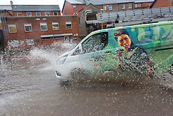 © Licensed to London News Pictures. 20/01/2021. Builth Wells, Powys, Wales, UK. Vehicles drive through a flooded road in Builth Wells, Powys, UK. After recent heavy rainfall the river Wye bursts it's banks at Builth Wells in Powys, Wales, UK. Photo credit: Graham M. Lawrence/LNP