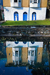Buildings reflected in the pond at Portmeirion village, designed and built by Sir Clough Williams-Ellis, Gwynedd, Wales, UK