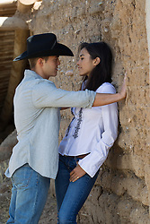 cowboy and a girl together on a ranch in New Mexico flirting and being seductive together