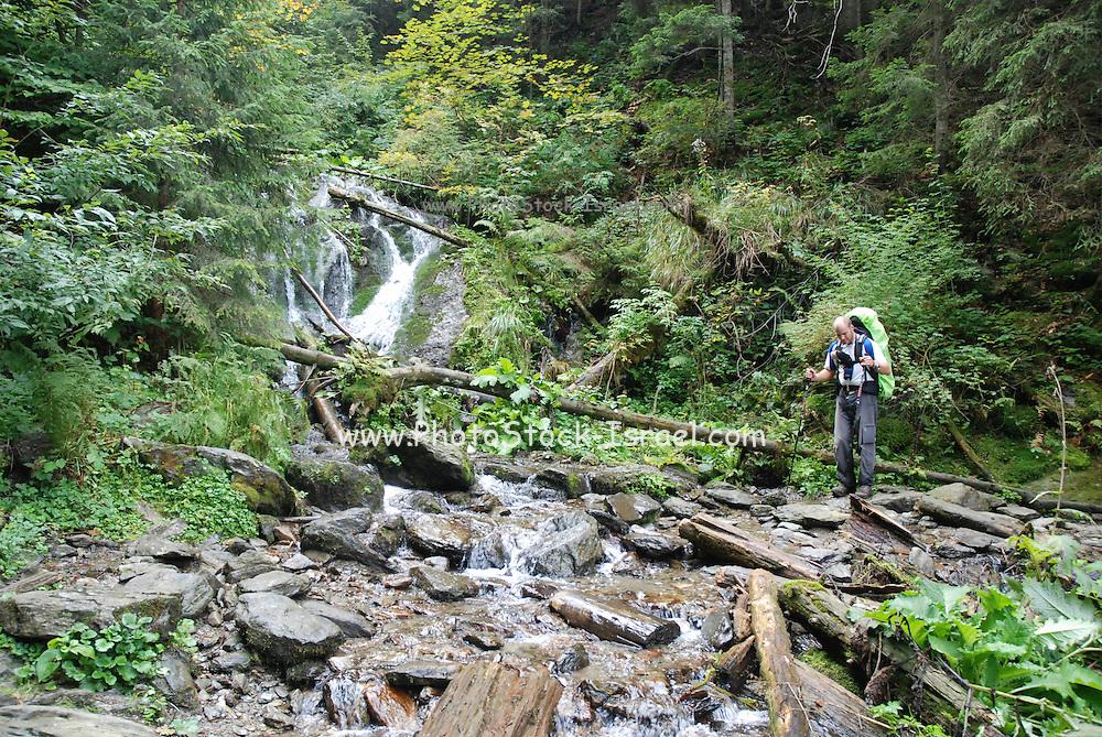 Romania, tourist hikes across a stream