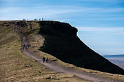 A group of adult and child ramblers walk along the dirt track along the summit of Pen Y Fan Mountain in Brecon Beacons National Park, Wales, Powys, United Kingdom. Pen Y Fan is the highest point in the Brecon Beacons hill and mountain range in South Wales. The National Park was established in 1957 due to the spectacular landscape which is rich in natural beauty.