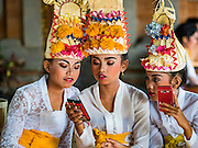 19 JULY 2016 - TAMPAKSIRING, GIANYAR, BALI, INDONESIA:  Dancers check their smart phones while they wait to perform on the first day of a ceremony to honor the anniversary Pura Agung temple, one of the most important Hindu temples on Bali. This year's ceremony is the most important in years because it falls on the 50 year cycle of the temple's founding. This year's ceremony lasts for 11 days.     PHOTO BY JACK KURTZ