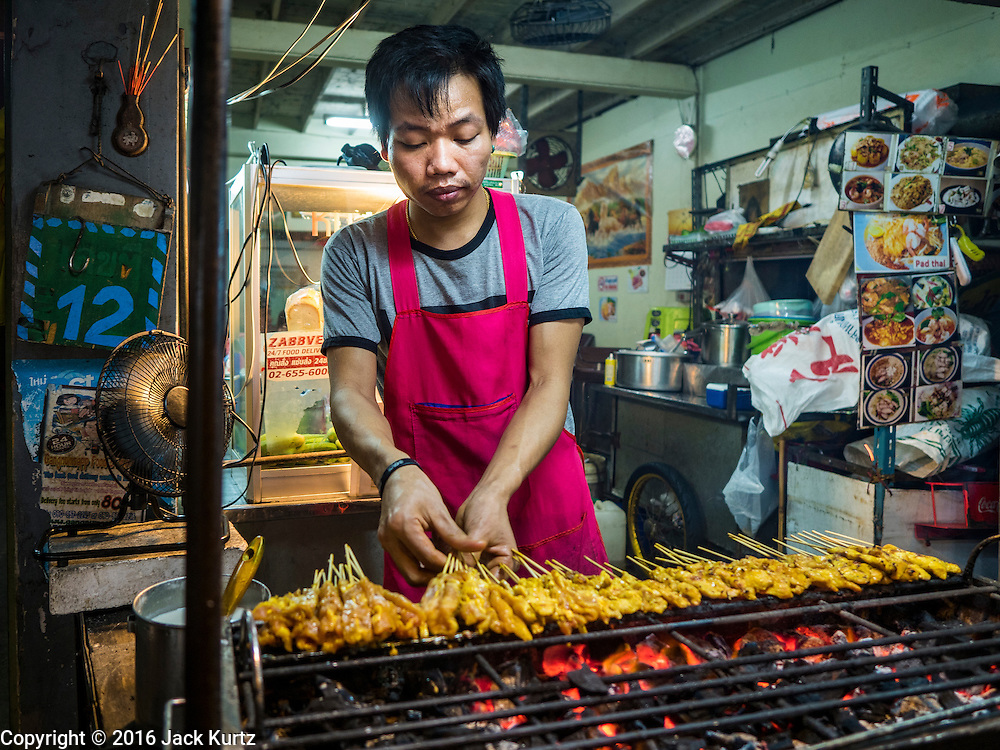 """17 JANUARY 2016 - BANGKOK, THAILAND: A food stall vendor grills chicken """"satae,"""" a marinted grilled meat on stick served with peanut sauce, on Sukhumvit Soi 38, one of the most famous street food areas in Bangkok. The food carts and small restaurants along the street have been popular with tourists and Thais alike for more than 40 years. The family that owns the land along the soi recently decided to sell to a condominium developer and not renew the restaurant owners' leases. More than 40 restaurants and food carts will have to close. Most of the restaurants on the street closed during the summer of 2015. The remaining restaurants are supposed to close by the end of this week.          PHOTO BY JACK KURTZ"""