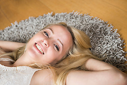 Portrait of a beautiful young woman lying on floor, Munich, Bavaria, Germany