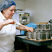 Cheesemaker, Kathy Biss turning the Cuillin Coulommier cheese onto a fresh mat and board at the West Highland Dairy in the village of Achmore by the Kyle of Lochalsh in the Scottish Highlands. Owned by Kathy and David Biss, West Highland Dairy was established in 1987 and as well as managing their own small commercial dairy business, they have taught a great number of prospective cheesemakers during the last 20 years.