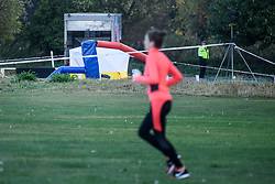 © Licensed to London News Pictures. 15/09/2019. London, UK. A woman jogs past the crime scene at a children's play area in Jubilee Park in Edmonton, North London where a man, reported to be 30 years old, has bene stabbed to death. A man in his 40's has been arrested. Photo credit: Ben Cawthra/LNP