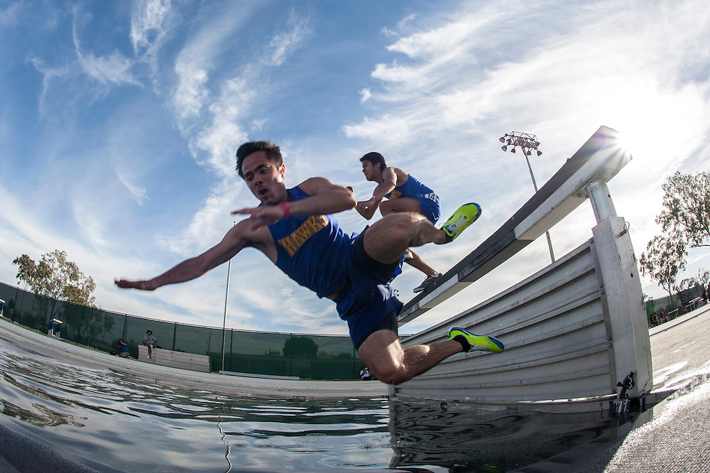 Ceasar Gallardo of Santiago Canyon College falls into the water pit during the 3000m steeplechase during the Long Beach State Classic at Cerritos College on March 2, 2013.