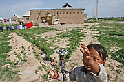 A girl reaches out to a water faucet in a village in Bishkek, Kyrgizstan.