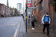 National coronavirus lockdown three begins in Birmingham city centre, which is deserted apart from a few people waiting at a bus stop in Digbeth on 6th January 2021 in Birmingham, United Kingdom. Following the recent surge in cases including the new variant of Covid-19, this nationwide lockdown, which is an effective Tier Five, came into operation today, with all citizens to follow the message to stay at home, protect the NHS and save lives.