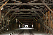 Trusses and beams in geometric shapes and car driving through covered bridge in New Hampshire, USA