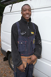 Young workman standing by his van,