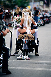 Just Married. Sturgis, SD. 1994<br /> <br /> Limited Edition Print from an edition of 50. Photo ©1994 Michael Lichter.<br /> <br /> The Story: I was just an innocent bystander as this wedding procession rode down Main Street.  Is there a side of everyone that wishes they were as unconventional as this couple appears to be?