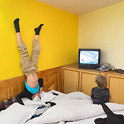 Two brothers watch TV, one of them doing a head stand.
