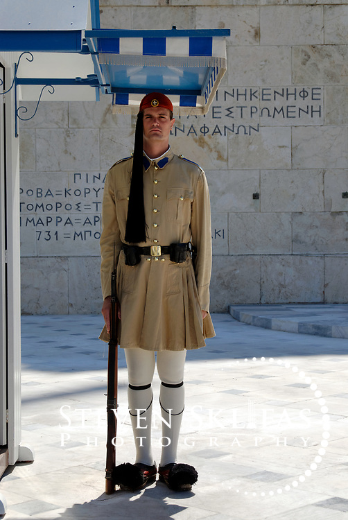 Syntagma square. Athens. Greece. View of an elite member of the Presidential ceremonial guard unit known as Evzones standing guard in front of the monument to the Unknown Soldier. The monument to the Unknown Soldier, erected in 1929-1932, depicts a relief of a dying Greek solider and is watched around the clock by Evzones standing motionless outside their sentry boxes wearing traditional dress. This guard is wearing the summer uniform tunic that is light khaki in colour.