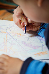 Close up of young boy drawing with colour pencil
