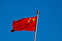 Chinese Flag flutters in the wind against a deep blue sky.