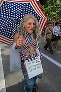 """An octogenarian woman bedecked in rded, white, nd blue marches with a sign which reads """"I'm age 82 but my parade is not thru."""""""