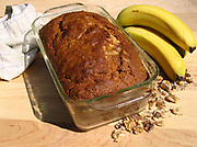 Loaf of banana nut bread on a butcher block counter with whole bananas sitting next to it