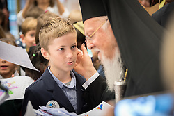 "21 November 2018, Geneva, Switzerland: Children from the Greek schools in Geneva and Lausanne hand over drawings to the Ecumenical Patriarch Bartholomew as a friendly gesture of welcome, as he arrives at the Ecumenical Centre. On the occasion of 2018 World Children's Day, and in recognition of the World Council of Churches' 70th anniversary, UNICEF and WCC convene a number of WCC member churches and common partners to celebrate the UNICEF-WCC global partnership and to take stock of the many achievements of the Churches' Commitments to Children. In line with the spirit of a day ""for children, by children,"" the celebratory event placed children at the centre by asking them to share their recent experiences as participants in the several Youth Talks on ending violence in schools that WCC member churches around the world have organized in recent years; hearing the perspective of young migrants supported by a church-run sponsorship project; and showcasing promising examples of how churches support children in climate justice activities."