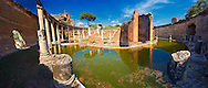 Hadrian's Villa ( Villa Adriana ) 2nd century AD - The Maritime Theatre (  Teatro Marittimo ), so called because of its shape and marine architectural decorations such as Tritons, is at the centre of Hadrian's Villa complex.  At its centre of the Teatro Marittimo is a circular islet surrounded  by a water filled moat which in turn is surrounded by a circular barrel vaulted portico with 40 Ionic columns. The circular building on the islet consisted of rooms that surrounded a central peristyle which was probably a retreat for Hadrian to escape to. Villa Adriana, Tivoli, Italy. A UNESCO World Heritage Site. .<br /> <br /> If you prefer to buy from our ALAMY PHOTO LIBRARY  Collection visit : https://www.alamy.com/portfolio/paul-williams-funkystock/hadrians-villa-tivoli.html<br /> Visit our CLASSICAL WORLD HISTORIC SITES PHOTO COLLECTIONS for more photos to buy as buy as wall art prints https://funkystock.photoshelter.com/gallery-collection/Classical-Era-Historic-Sites-Archaeological-Sites-Pictures-Images/C0000g4bSGiDL9rw