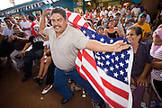 July 13, 2008 -- PHOENIX, AZ: Lucha Libre fans wave an American flag during a Lucha Libre show at El Gran Mercado in Phoenix. Lucha Libre is Mexican style wrestling. There are heros (Tecnicos) and villians (Rudos). The masks are popular as children's gifts and tourist mementos. As the size of the Mexican community in the Phoenix area has grown, attendance at the Lucha Libre shows has increased. Lucha Libre differs from American style entertainment wrestling in several ways, but principally the wrestlers are more acrobatic and rely less on body slams than American wrestling. The shows, which used to be held only periodically, are now held every week at El Gran Mercado, a flea market and swap meet that caters mostly to the Mexican community in Phoenix.   Photo by Jack Kurtz / ZUMA Press