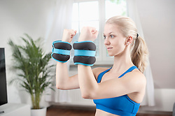 Young woman lifting weights in living room, Bavaria, Germany
