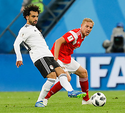 June 19, 2018 - Saint Petersburg, Russia - Yury Gazinsky (R) of Russia national team and Mohamed Salah of Egypt national team vie for the ball during the 2018 FIFA World Cup Russia group A match between Russia and Egypt on June 19, 2018 at Saint Petersburg Stadium in Saint Petersburg, Russia. (Credit Image: © Mike Kireev/NurPhoto via ZUMA Press)