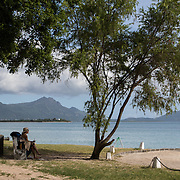 A woman sits near the beach with mountains in the background. This beach is called La Preneuse Beach and is a quiet little beach in the southwest with a nice public beach access.