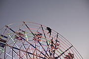 A Fairground Wheels without electricity or any kind of motor, the wheel is moved by half a dozen teenagers climming up the iron structure, in the Taunggyi Ballon Festival Fair,  Taunggyi, Myanmar.<br />