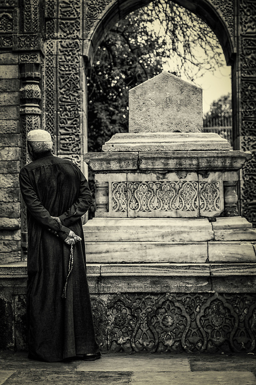 A pilgrim at the cenotaph of the Delhi Sultanate ruler, Iltutmish in Qutb Minar Complex in New Delhi, India. The tomb of Iltutmish was the first Islamic tomb to be built in India.