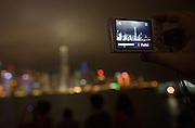 A tourist takes a photo of the Hong Kong skyline at night.