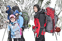 A family snowshoes along the Rainier Vista Trail of the Mount Tahoma Trails crosscountry ski and snowshoe hut-to-hut trail system in the Cascade Range near Mount Rainier, Washington state, USA.