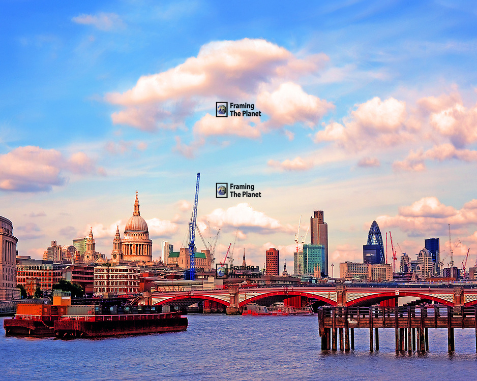 This is a photograph showing the famous City area of London. Included are St Paul's Cathedral, NatWest Tower (no. 42), the Gherkin and Blackfriers bridge from the river Thames. There is a strong blue sky with perfect white clouds over the heart of the UK finance centre of this urban metropolis. This image was taken from the South Bank as is one of the most famous views in the British capitol.