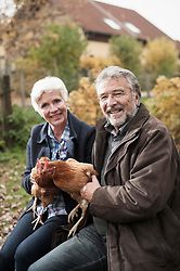 Mature couple holding chicken birds in the farm, Bavaria, Germany