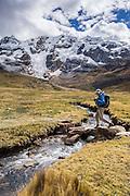 Trekkers cross a stream under Nevado Carnicero (19,500 ft or 5960 m) near Carnicero settlement in the Cordillera Huayhuash, Andes Mountains, Peru, South America. Day 3 of 9 days trekking around the Cordillera Huayhuash.