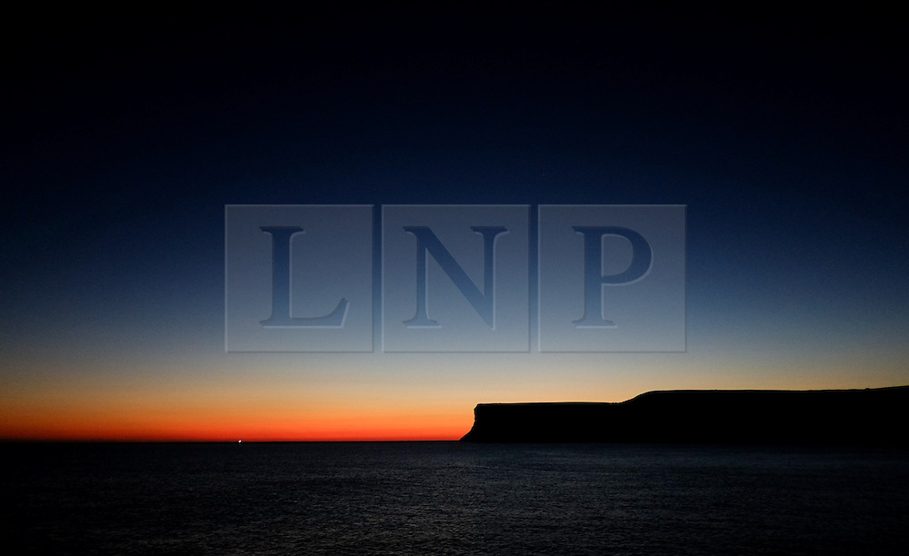 © Licensed to London News Pictures. <br /> 12/10/2014. <br /> <br /> Saltburn, United Kingdom<br /> <br /> The first light of morning spreads out in the sky over Huntcliff in Saltburn by the Sa<br /> <br /> Photo credit : Ian Forsyth/LNP