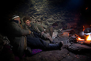 A kyrgyz caravan leader (left) named Abdul Hameed, on his way down to Sarhad, talking with Wakhi trader..Wakhi shepherd life inside the winter hut of Sap...Trekking up the Wakhan frozen river, the only way up to reach the high altitude Little Pamir plateau, home of the Afghan Kyrgyz community.