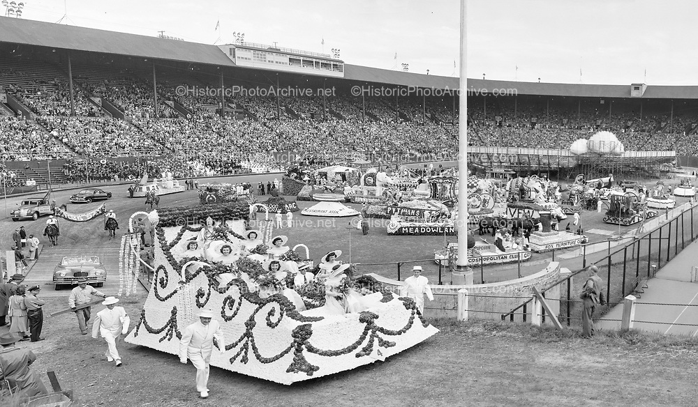 """June 9, 1950. """"STADIUM. Hundreds of thousands of blooms and untold labor went into the construction of the floats that appeared early Friday in Multnomah stadium, where the judging was done for the Grand Floral parade that climaxed annual Portland Rose Festival.""""  (on the left exiting the stadium is the Queen's float carrying the queen and her princesses)"""