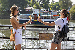 Licensed to London News Pictures. 05/09/2021. London, UK. Left, Deirbhile Cleary 25 and Autumn Brown 29 from Twickenham enjoy an ice-cream in the sunshine along the Thames at Richmond, south-west London as weather forecaster predict a mini-heatwave for September from today with temperatures hitting over 27c tomorrow and throughout the week. Photo credit: Alex Lentati/LNP